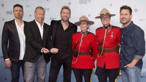 Members of Nickelback pose with RCMP officers on the red carpet at the Juno awards in Calgary, Sunday, April 3, 2016. Many jokes have been made at the expense of scorned arena rockers Nickelback, but it took an unwelcome meme from divisive U.S. President Donald Trump to rally public support for the oft-maligned Canadian band. THE CANADIAN PRESS/Jeff McIntosh