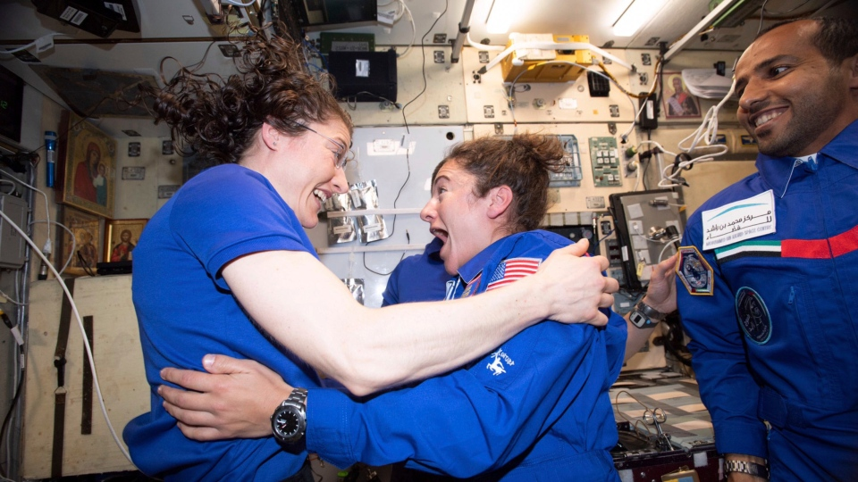 In this photo made available by NASA astronaut Jessica Meir on Sept. 29, 2019, Christina H. Koch, left, and Meir greet each other after Meir's arrival on the International Space Station. On Friday, Sept. 4, 2019, NASA announced that the International Space Station's two women will pair up for a spacewalk on Oct. 21 to plug in new batteries. (NASA via AP)