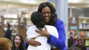 "Former first lady Michelle Obama embraces a student at her alma mater, Whitney M. Young Magnet High School, on Chicago's West Side, Monday, Nov. 12, 2018, a day before the launch of a book tour to promote her memoir, ""Becoming."" (AP Photo/Teresa Crawford)"