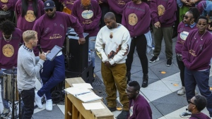 """Kanye West, center, bows his head in prayer during his """"Sunday Service"""" at The Gateway in Salt Lake City on Saturday, Oct. 5, 2019. Thousands packed into the outdoor mall, causing people to stand on and climb up anything they could find to catch a glimpse of West. (Colter Peterson/The Deseret News via AP)"""