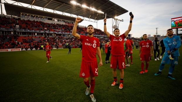 Toronto FC midfielder Jonathan Osorio (21) and teammate Marco Delgado (8) celebrate towards fans after MLS soccer action against the Columbus Crew SC, in Toronto, Sunday, Oct. 6, 2019. THE CANADIAN PRESS/ Cole Burston