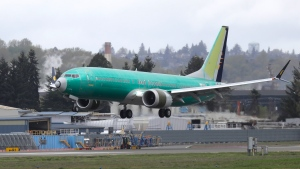 FILE - In this April 10, 2019 photo, a Boeing 737 MAX 8 airplane being built for India-based Jet Airways lands following a test flight at Boeing Field in Seattle. Boeing and the Federal Aviation Administration are both partly at fault for the failures of the 737 Max, the plane model involved in two fatal crashes, according to a new report. (AP Photo/Ted S. Warren, File)