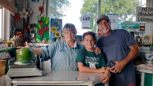 This Dec. 13, 2018 photo provided by Juliane Pokini shows the first weigh in at Kula Country Farms showing employee Meridyth Sealey, left, with Lo'ihi Pokini and his father Mark Pokini in their kitchen at Kula Country Farms in Kula, Hawaii. The Pokini family from the island of Maui received the Guinness certificate this week for the avocado weighing 5.6 pounds (2.54 kilograms), The Maui News reported Thursday, Oct. 11, 2019. (Juliane Pokini via AP)