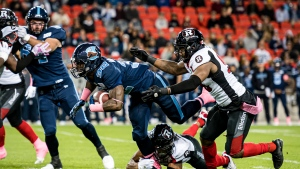 Toronto Argonauts running back James Wilder Jr. (32) is stopped by Ottawa Redblacks defensive lineman Kene Onyeka (99) and Ottawa Redblacks defensive back Kishawn McClain (33) during first half CFL football action in Toronto on Friday, Oct. 11, 2019. THE CANADIAN PRESS/Christopher Katsarov