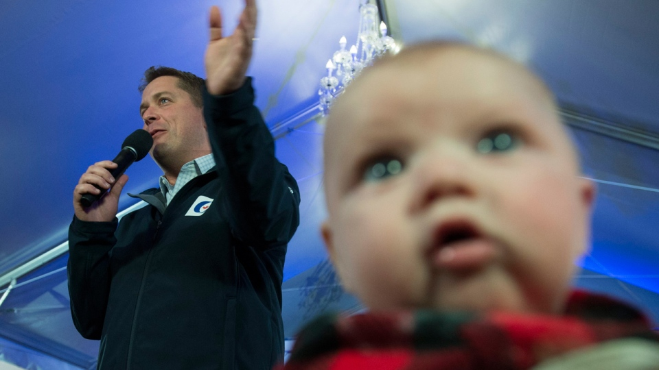 Four-month-old Ronnie Nickel looks on as Conservative leader Andrew Scheer addresses a rally during a campaign stop in Langley, B.C. Friday, October 11, 2019.  THE CANADIAN PRESS/Jonathan Hayward