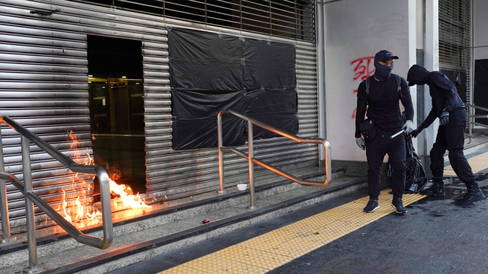 Protesters throw molotov cocktail to the entrance of MTR station during a protest in Hong Kong, Saturday, Oct. 12, 2019. Protesters marching peacefully hit the rain-slickened streets of Hong Kong again in multiple locations on Saturday, defying police warnings that they were gathering illegally. (AP Photo/Vincent Yu)