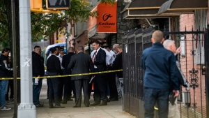 NYPD investigates the scene of a shooting in the Brooklyn borough of New York on Saturday, Oct. 12, 2019.  Authorities responded to a call about shots fired just before 7 a.m. and found four men dead in the Crown Heights neighborhood of Brooklyn at an address that corresponds to a private social club according to an online map of the street.  A woman and two men suffered non-life-threatening injuries.  (AP Photo/Jeenah Moon)
