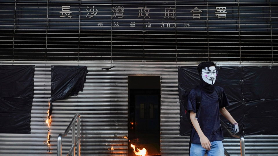 A protester throws molotov cocktail to the entrance of MTR station during a protest in Hong Kong, Saturday, Oct. 12, 2019. Protesters marching peacefully hit the rain-slickened streets of Hong Kong again in multiple locations on Saturday, defying police warnings that they were gathering illegally. (AP Photo/Vincent Yu)