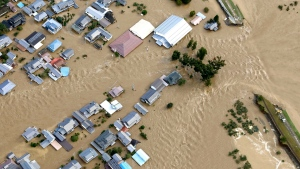 Residential area is seen in muddy waters after an embankment of the Chikuma River broke because of Typhoon Hagibis, in Nagano, central Japan, Sunday, Oct. 13, 2019. Rescue efforts for people stranded in flooded areas are in full force after a powerful typhoon dashed heavy rainfall and winds through a widespread area of Japan, including Tokyo.(Yohei Kanasashi/Kyodo News via AP)