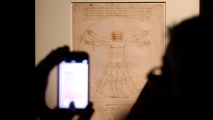 """FILE - In this Tuesday April 14, 2015 file photo, Leonardo da Vinci's """"Vitruvian Man"""" is displayed during an exhibition in Milan, Italy. An Italian court has ruled that Leonardo Da Vinci's iconic Vitruvian Man drawing can be loaned to France's Louvre, solving a long-going cultural dispute between Italy and France. The Venice court last week had suspended the loan of the world-famous drawing, which is part of a batch of works by Leonardo and Raphael that the Italian government had agreed to send to Paris. Wednesday's ruling cleared the way to the loan, rejecting a complaint filed by an Italian heritage group, Italia Nostra (Our Italy), which contended that the drawing was too fragile to travel and risked being damaged. (Matteo Bazzi/ANSA via AP) The Associated Press"""