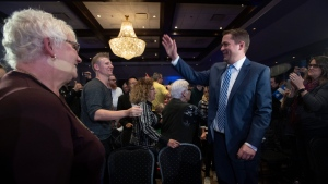 Conservative Leader Andrew Scheer's mother-in-law Barb Ryan, left, looks on as he enters the room to deliver a campaign speech in La Prairie, Que., Tuesday, Oct. 15, 2019. THE CANADIAN PRESS/Adrian Wyld
