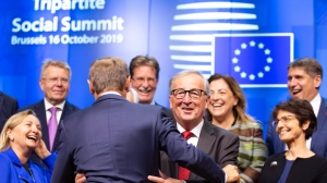 European Commission President Jean-Claude Juncker, front center right, and European Council President Donald Tusk, front center left, change places prior to a group photo during a tripartite summit in Brussels, Wednesday, Oct. 16, 2019. European Union and British negotiators have failed to get a breakthrough in the Brexit talks during a frantic all-night session and will continue seeking a compromise on the eve of Thursday's crucial EU summit. (AP Photo/Virginia Mayo)