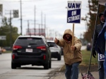 A member of UAW Local 1005 gives a thumbs up to drivers outside GM Parma plant on Brookpark Road on Wednesday, Oct. 16, 2019, in Parma, Ohio. Bargainers for General Motors and the United Auto Workers reached a tentative contract deal on Wednesday that could end a monthlong strike that brought the company's U.S. factories to a standstill. (Gus Chan/The Plain Dealer via AP)