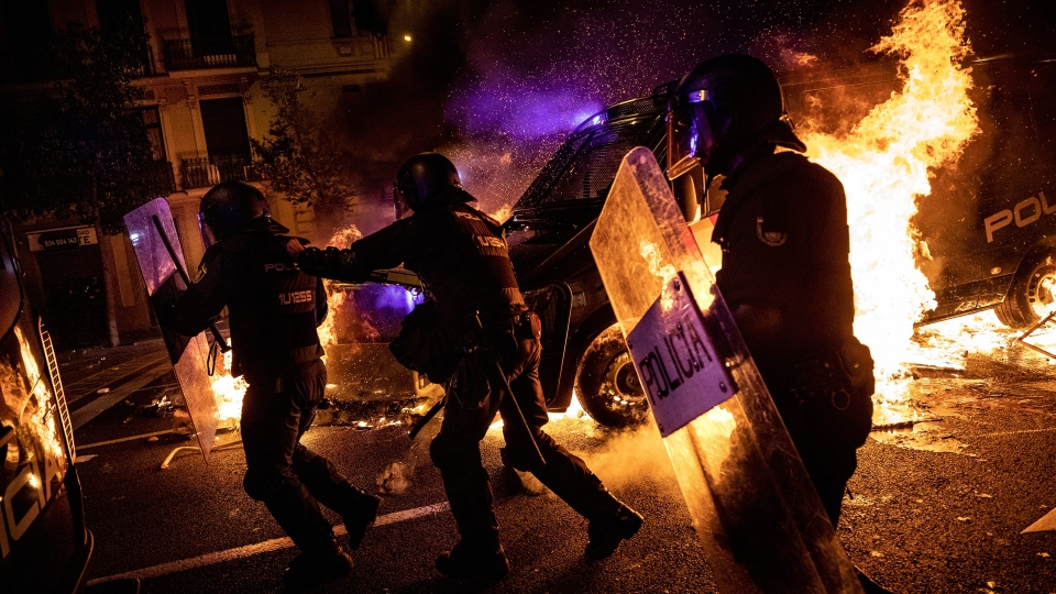 Policemen run as a police van drives over a burning barricade during clashes between protestors and police in Barcelona, Spain, Wednesday, Oct. 16, 2019. Spain's government said Wednesday it would do whatever it takes to stamp out violence in Catalonia, where clashes between regional independence supporters and police have injured more than 200 people in two days. (AP Photo/Bernat Armangue)
