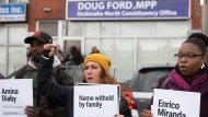 Protesters stand outside the constituency office of Ontario Premier Doug Ford, in Toronto, Wednesday, Oct. 16, 2019. Protesters occupied the offices demanding that the Premier signs a section of the Workplace Safety Act to help prevent workplace deaths and injuries. THE CANADIAN PRESS/Chris Young