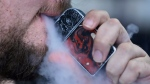 FILE - In this Friday, Oct. 4, 2019 photo, a man using an electronic cigarette exhales in Mayfield Heights, Ohio. Vaping-related illnesses in the U.S. are still rising, though at a slightly slower pace.  (AP Photo/Tony Dejak)