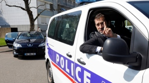 "In this April 11, 2019 file photo, French Interior Minister Christophe Castaner gestures from a police car as he visits the Neuhof district of Strasbourg, eastern France. One person is in French custody on preliminary terrorism charges after threatening a Sept. 11-style plane hijacking and attack. Christophe Castaner said on France-2 television Thursday Oct. 17, 2019 night that the person was arrested Sept. 26 while ""in the process of planning"" such an attack. (AP Photo/Jean-Francois Badias, File)"