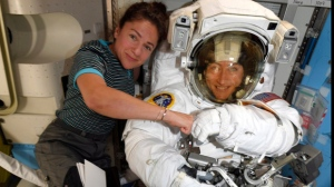 In this image released Friday, Oct. 4, 2019, by NASA, astronauts Christina Koch, right, and, Jessica Meir pose for a photo on the International Space Station. NASA has moved up the first all-female spacewalk to Thursday, Oct. 17, 2019, or Friday because of a power system failure at the International Space Station.  (NASA via AP)