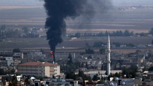 In this photo taken from the Turkish side of the border between Turkey and Syria, in Ceylanpinar, Sanliurfa province, southeastern Turkey, smoke billows from a fire in Ras al-Ayn, Syria, Friday, Oct. 18, 2019.