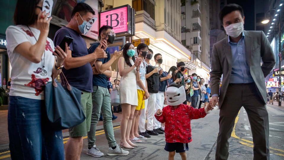 A boy wearing a mask walks past a line of protestors in Hong Kong, Friday, Oct. 18, 2019. Hong Kong pro-democracy protesters are donning cartoon and superhero masks as they formed a human chain across the semiautonomous Chinese city, in defiance of a government ban on face coverings. (AP Photo/Mark Schiefelbein)