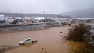 In this image made from video provided by Russian Emergency Situations Ministry press service, a view after the collapse during heavy rain occurred early Saturday near the village of Shchetinkino, in the Krasnoyarsk region about 3,400 Km (2,100 miles) east of Moscow, Russia, Saturday, Oct. 19, 2019.  Russian emergency officials say at least 15 people are dead after a dam at a Siberian gold mine collapsed and water flooded two workers' dormitories, 13 people were unaccounted for, Russian news agencies reported. (Russian Ministry of Emergency Situations press service via AP)