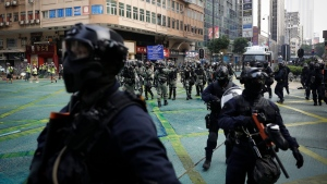 Police arrive to disperse protestors in Hong Kong, Sunday, Oct. 20, 2019. Protesters again flooded streets on Sunday, ignoring a police ban on the rally and setting up barricades amid tear gas and firebombs. (AP Photo/Mark Schiefelbein)