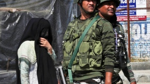 A Kashmiri woman walks past paramilitary soldiers standing guard near the site of a gunbattle in Bijbehara, south of Srinagar, Indian controlled Kashmir, Wednesday, Oct. 16, 2019. Indian police officer Parvaiz Ahmed said Indian security forces killed three militants in an exchange of gunfire in southern Kashmir, following intelligence that a group of militants was hiding in Bijbehara town. Indian-administered Kashmir has experienced unrest and sporadic anti-government protests since New Delhi revoked its special status. MUKHTAR KHAN AP PHOTO