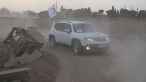 In this image provided by Turkish Red Crescent, Turkish Red Crescent vehicles arrive to deliver aid to Syrians in Ras Al-Ayn, Syria, Saturday, Oct. 19, 2019. Turkish Red Crescent says it has delivered humanitarian aid for 2000 people in Ras Al-Ayn, including flour with other food and hygiene materials to follow. The organisation said it also provided aid to Tal Abyad and will continue to do so in areas cleared by the Turkish and the Turkish-backed forces, from fighters from Kurdish People's Protection Units, or YPG. (Fatih Isci/Turkish Red Crescent via AP)