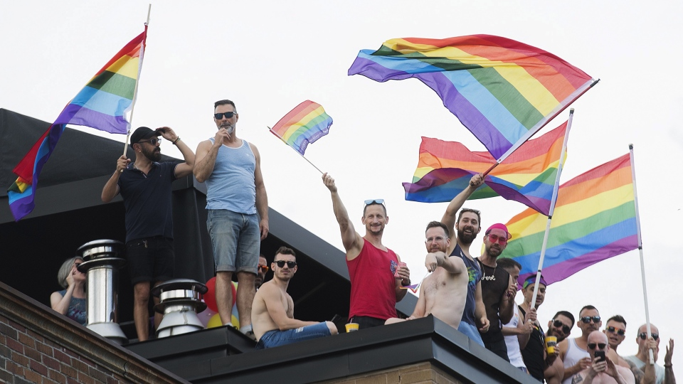 People wave rainbow flags during the annual Pride parade in Montreal, Sunday, August 18, 2019. THE CANADIAN PRESS/Graham Hughes