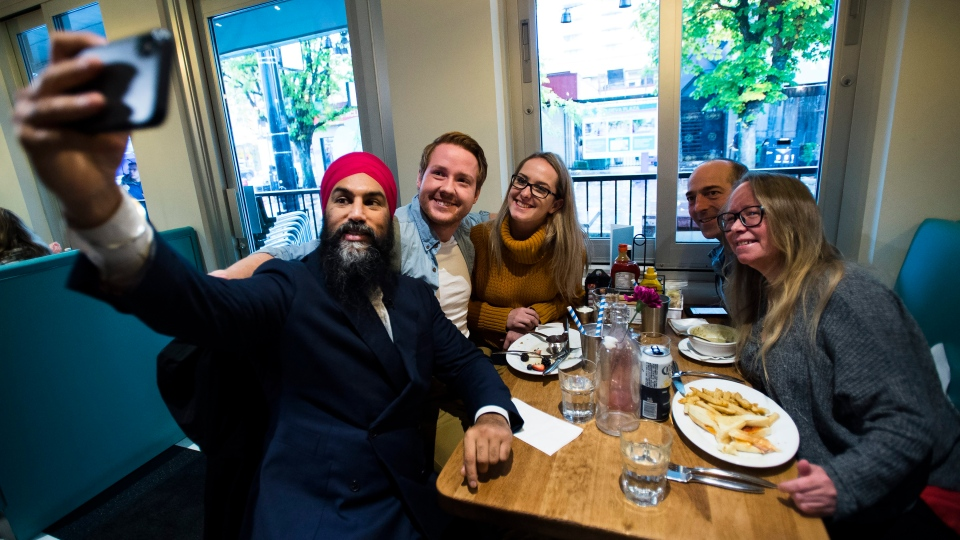 NDP leader Jagmeet Singh poses for a selfie with people in a restaurant in Davie Village during a campaign stop in Vancouver, B.C., on Sunday, October 20, 2019. THE CANADIAN PRESS/Nathan Denette