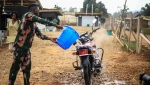 Motorcycle taxi driver Germain Kalubenge pours chlorinated water on his motorcycle after taking a suspected case of Ebola to an Ebola transit center where potential cases are evaluated, in Beni, Congo, Thursday, Aug. 22, 2019. Kalubenge is a rare motorcycle taxi driver who is also an Ebola survivor in eastern Congo, making him a welcome collaborator for health workers who have faced deep community mistrust during the second deadliest Ebola outbreak in history. (AP Photo/Al-hadji Kudra Maliro)