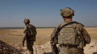 FILE - In this Sept. 6, 2019 file photo, U.S. soldiers survey the the safe zone between Syria and the Turkish border near Tal Abyad, Syria, on a joint patrol with the Tax Abyad Military Council, affiliated with the U.S.-backed Syrian Democratic Forces.  (AP Photo/Maya Alleruzzo, File)