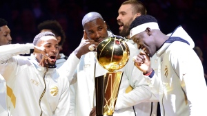 Toronto Raptors players Norman Powell, left to right, Serge Ibaka, Marc Gasol and Pascal Siakam stand with their rings behind the Larry O'Brien NBA Championship Trophy before playing the New Orleans Pelicans in Toronto on Tuesday Oct. 22, 2019. The Raptors defeated the Golden State Warriors last spring in a six-game final to win the NBA title for the first time in franchise history. THE CANADIAN PRESS/Frank Gunn
