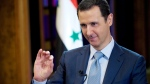 FILE - In this Feb. 10, 2015, file photo released by the Syrian official news agency SANA, Syrian President Bashar Assad gestures during an interview in Damascus, Syria. (SANA via AP, File)