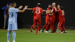 Toronto FC celebrates the first of two goals by Alejandro Pozuelo as New York City FC's Ismael Tajouri (29) gestures during the second half of an MLS Eastern Conference semifinal soccer match Wednesday, Oct. 23, 2019, in New York. Toronto won 2-1. (AP Photo/Frank Franklin II)