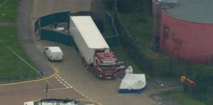 In this Oct. 23, 2019, file photo, police forensic officers attend the scene after a truck was found to contain a large number of dead bodies in Thurrock, South England. The discovery in England of the bodies of 39 people believed to be from China lays bare some crucial but sometimes overlooked facts about China's development as a rising global power that has elevated hundreds of millions of its citizens to the middle classes. (UK Pool via AP, File)