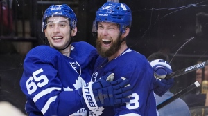 Toronto Maple Leafs' Ilya Mikheyev (65) congratulates teammate Jake Muzzin after he scored against the San Jose Sharks during second period NHL hockey action in Toronto on Friday, Oct. 25, 2019. THE CANADIAN PRESS/Hans Deryk