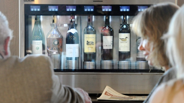 Patrons sit in front of a state-of-the-art wine serving & preserving system, that keeps bottles of wine at their optimal serving condition at the Plum Market Wine Bar & Cafe on May 16, 2016 at Detroit Metropolitan Airport in Romulus, Mich. (Daniel Mears/Detroit News via AP)
