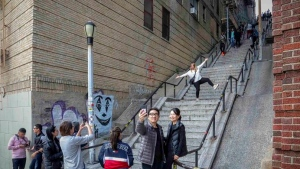 "People pose on the steps between two apartment buildings, Monday Oct. 28, 2019, in the Bronx borough of New York. The stairs have become a tourist attraction in recent weeks since the release of the movie ""Joker."" In the movie, lead actor Joaquin Phoenix dances as he goes down the steps, wearing a bright red suit and clown makeup. (AP Photo/Bebeto Matthews)"