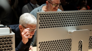 In this June 3, 2019, file photo Apple CEO Tim Cook, left, and chief design officer Jonathan Ive look at a Mac Pro in the display room at the Apple Worldwide Developers Conference in San Jose, Calif. Apple Inc. reports financial earns on Wednesday, Oct. 30. (AP Photo/Jeff Chiu, File)