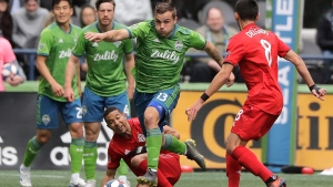 Seattle Sounders forward Jordan Morris (13) leaps over Toronto FC defender Justin Morrow, lower center, as he drives with the ball during the second half of an MLS soccer match, Saturday, April 13, 2019, in Seattle. The Sounders will play Toronto FC in the 2019 MLS Cup in Seattle on Nov.10. THE CANADIAN PRESS/AP/Ted S. Warren