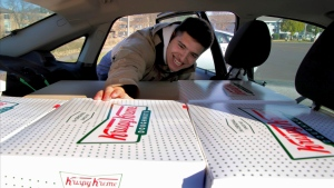 In this Saturday, Oct. 26, 2019 photo, Jayson Gonzalez reaches into his car for another box of Krispy Kreme doughnuts for customers in Little Canada, Minn, who ordered online. (Deanna Weniger/Pioneer Press via AP)