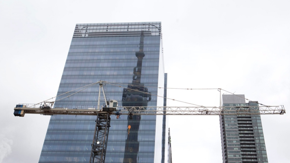 The CN tower is reflected in a high rise building behind a construction crane in downtown Toronto on February 4, 2012. THE CANADIAN PRESS/Pawel Dwulit