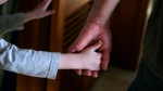 A man and child hold hands in Springfield, Mass. in a Saturday, Dec. 12, 2015 photo. Family caregivers in Ontario now have a help line if they're needing respite, a support group or information on issues including tax credits. THE CANADIAN PRESS/AP/Charles Krupa