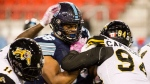 Toronto Argonauts offensive lineman Isiah Cage (66) is stopped by Hamilton Tiger-Cats defensive end Justin Capicciotti (94) during second half CFL football action in Toronto on Friday, Oct. 12, 2018. THE CANADIAN PRESS/Christopher Katsarov