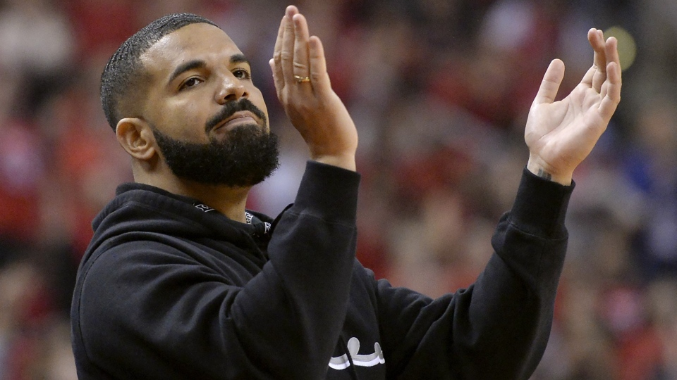 """Toronto-born performer Aubrey """"Drake"""" Graham cheers from courtside during first half NBA Eastern Conference finals action between the Toronto Raptors and the Milwaukee Bucks, in Toronto on Saturday, May 25, 2019. THE CANADIAN PRESS/Nathan Denette"""