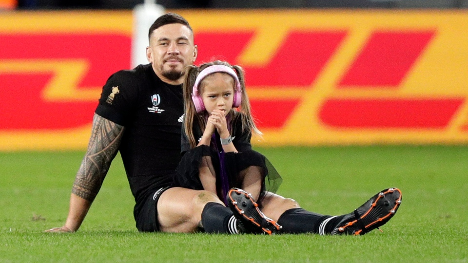 New Zealand's Sonny Bill Williams sits on the field with daughter after the Rugby World Cup bronze final game at Tokyo Stadium between New Zealand and Wales in Tokyo, Japan, Friday, Nov. 1, 2019. THE CANADIAN PRESS/AP-Mark Baker