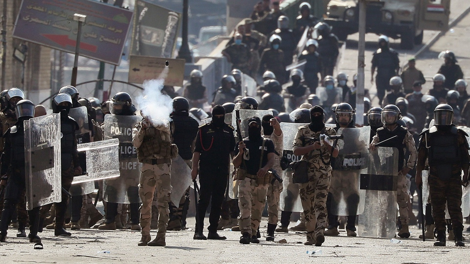 Iraqi riot police fire tear gas to disperse anti-government protesters gathering on the al- Shuhada (Martyrs) bridge in central Baghdad, Iraq, Thursday, Nov. 7, 2019. Iraqi security forces opened fire on Thursday, killing several protesters as they were trying to remove barriers blocking their march in central Baghdad, while in the south, demonstrators forced the closing of the country's main port, hours after services had resumed following days of closure, officials said. (AP Photo/Hadi Mizban)