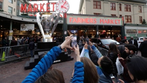 People take photos of a giant replica of the MLS Cup trophy, Friday, Nov. 8, 2019, on display at Pike Place Market in Seattle. Toronto FC is scheduled to face the Seattle Sounders on Sunday in the MLS Cup soccer match in Seattle, the third time the two teams will have met for the MLS championship. (AP Photo/Ted S. Warren)