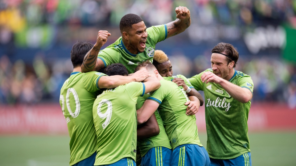 Teammates mob Seattle Sounders defender Kelvin Leerdam, centre, (obscured) after scoring against the Toronto FC during second half MLS Cup soccer action in Seattle on Sunday, Nov. 10, 2019. THE CANADIAN PRESS/Jonathan Hayward